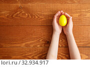 Купить «Painted Easter Egg In Hands Wooden Background», фото № 32934917, снято 25 марта 2019 г. (c) Иван Карпов / Фотобанк Лори