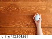 Купить «Painted Easter Egg In Hands Wooden Background», фото № 32934921, снято 25 марта 2019 г. (c) Иван Карпов / Фотобанк Лори