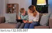 Купить «mother and son using tablet computer at home», видеоролик № 32935097, снято 23 декабря 2019 г. (c) Syda Productions / Фотобанк Лори