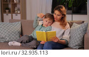 Купить «happy mother and son reading book sofa at home», видеоролик № 32935113, снято 23 декабря 2019 г. (c) Syda Productions / Фотобанк Лори