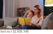 Купить «happy mother and son reading book sofa at home», видеоролик № 32935145, снято 23 декабря 2019 г. (c) Syda Productions / Фотобанк Лори