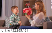 smiling little son gives flowers to mother at home. Стоковое видео, видеограф Syda Productions / Фотобанк Лори