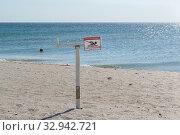 Купить «Запрещающая купание табличка на берегу моря. Песчаный пляж и голубая вода. При несчастных случаях на воде звонить 112», фото № 32942721, снято 10 сентября 2019 г. (c) Наталья Гармашева / Фотобанк Лори