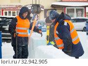Workers in winter workwear installing ice panels (2019 год). Редакционное фото, фотограф Андрей Кузнецов / Фотобанк Лори