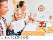 Kinder in Familie malen ihr Traumhaus als Eigenheim Wunsch vor dem Umzug. Стоковое фото, фотограф Zoonar.com/Robert Kneschke / age Fotostock / Фотобанк Лори
