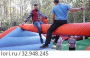 Купить «Guys having funny wrestling by pillows on inflatable beam in outdoor amusement playground», видеоролик № 32948245, снято 12 ноября 2019 г. (c) Яков Филимонов / Фотобанк Лори