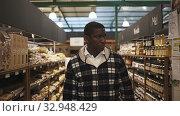 Купить «Portrait of adult African man choosing products in organic food store», видеоролик № 32948429, снято 5 апреля 2020 г. (c) Яков Филимонов / Фотобанк Лори