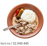 Russian cuisine dish - fork in Beef Stroganoff (Beef Stroganov, Befstroganov) pieces of stewed meat in sour cream with boiled rice on brown plate isolated on white background. Стоковое фото, фотограф Zoonar.com/Valery Voennyy / easy Fotostock / Фотобанк Лори