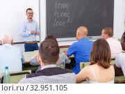 Купить «Young lecturer talking to mixed age students», фото № 32951105, снято 28 июня 2018 г. (c) Яков Филимонов / Фотобанк Лори