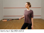 Female player with squash racket and ball on court. Стоковое фото, фотограф Tryapitsyn Sergiy / Фотобанк Лори