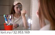 A young woman applying a face mask on her face. Стоковое видео, видеограф Константин Шишкин / Фотобанк Лори