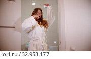 A young happy woman brushing her teeth at the morning wearing a bathrobe. Стоковое видео, видеограф Константин Шишкин / Фотобанк Лори