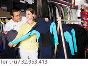 Купить «Couple searching wetsuits for surf», фото № 32953413, снято 7 октября 2019 г. (c) Яков Филимонов / Фотобанк Лори