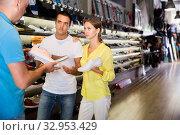 Купить «Young couple choosing sneakers with help of shop assistant in showroom», фото № 32953429, снято 7 октября 2019 г. (c) Яков Филимонов / Фотобанк Лори