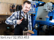 Positive man worker using instruments for fixing shoe. Стоковое фото, фотограф Яков Филимонов / Фотобанк Лори