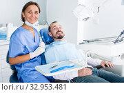 Man is satisfied in chair after treatment in dental office. Стоковое фото, фотограф Яков Филимонов / Фотобанк Лори