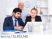 Купить «Employees are demonstrating reports on laptop to mature boss», фото № 32953545, снято 27 июня 2017 г. (c) Яков Филимонов / Фотобанк Лори