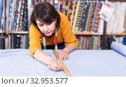 Купить «Saleswoman measuring and cutting off piece of cloth», фото № 32953577, снято 7 февраля 2019 г. (c) Яков Филимонов / Фотобанк Лори