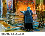 MTSKHETA, GEORGIA - OCT 25, 2018: Woman praying in Svetitskhoveli Cathedral in the historic town of Mtskheta, Georgia. Стоковое фото, фотограф Zoonar.com/monticello / easy Fotostock / Фотобанк Лори