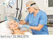 Купить «Professional cosmetician examining face skin of mature woman in clinic of esthetic cosmetology», фото № 32962073, снято 14 марта 2019 г. (c) Яков Филимонов / Фотобанк Лори