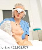 Professional cosmetician examining face skin of mature woman in clinic of esthetic cosmetology. Стоковое фото, фотограф Яков Филимонов / Фотобанк Лори