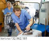 Купить «Workers ironing clothes after cleaning», фото № 32962181, снято 22 января 2019 г. (c) Яков Филимонов / Фотобанк Лори
