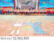 Купить «Russia Samara May 2019: graduates of a school, written on asphalt, a boy and a girl, against the background of a jubilant crowd of graduates at a city open holiday, for parents of teachers», фото № 32962805, снято 24 мая 2019 г. (c) Акиньшин Владимир / Фотобанк Лори