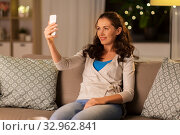 Купить «happy woman taking selfie with smartphone at home», фото № 32962841, снято 29 ноября 2019 г. (c) Syda Productions / Фотобанк Лори