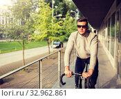 Купить «young man riding bicycle on city street», фото № 32962861, снято 21 августа 2016 г. (c) Syda Productions / Фотобанк Лори