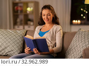young woman reading book at home in evening. Стоковое фото, фотограф Syda Productions / Фотобанк Лори