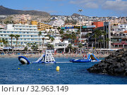 Tenerife, Spain - October 15, 2019: People enjoy water amusements on the Los Cristianos coastline, touristic town, situated on south coast of Canary Islands, Spain. Редакционное фото, фотограф Alexander Tihonovs / Фотобанк Лори