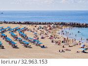 Tenerife, Spain - October 13, 2019: Vacationers people sunbathing on sandy beach of Playa de los Cristianos, enjoy warm Atlantic Ocean waters, Tenerife, Canary Islands, Spain. Редакционное фото, фотограф Alexander Tihonovs / Фотобанк Лори