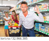 Купить «Anger male customer with family and purchases in shopping cart», фото № 32966385, снято 11 июля 2017 г. (c) Яков Филимонов / Фотобанк Лори