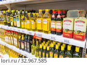 Купить «Russia Samara December 2019: Shelves with sunflower oil in a supermarket. Text in Russian: olive oil, discount, for frying, stewing, and baking, a touch of the Mediterranean», фото № 32967585, снято 25 декабря 2019 г. (c) Акиньшин Владимир / Фотобанк Лори