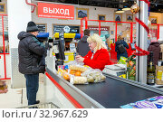 Купить «Russia, Samara, December 2019: Buyers pay for purchases at the box office in the store. Text in Russian: exit, to exit, scan your check, dry cleaning», фото № 32967629, снято 25 декабря 2019 г. (c) Акиньшин Владимир / Фотобанк Лори