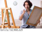 Купить «Young handsome man enjoying painting at home», фото № 32968229, снято 24 мая 2019 г. (c) Elnur / Фотобанк Лори