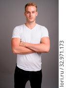Купить «Studio shot of young handsome man with blond hair wearing white shirt against gray background», фото № 32971173, снято 25 января 2020 г. (c) easy Fotostock / Фотобанк Лори