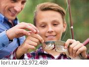 Teenager boy looking at fish on hook. Стоковое фото, фотограф Яков Филимонов / Фотобанк Лори