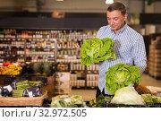 Купить «Customer buying cabbage at supermarket», фото № 32972505, снято 9 октября 2019 г. (c) Яков Филимонов / Фотобанк Лори