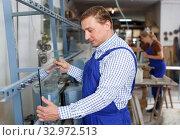 Купить «Worker and straight line chamfering machine», фото № 32972513, снято 10 сентября 2018 г. (c) Яков Филимонов / Фотобанк Лори