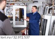Купить «Production worker in coverall demonstrating different PVC windows to customer», фото № 32972537, снято 30 марта 2017 г. (c) Яков Филимонов / Фотобанк Лори