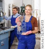 Купить «Female worker demonstrating drilled glass», фото № 32972613, снято 10 сентября 2018 г. (c) Яков Филимонов / Фотобанк Лори