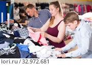 Young family of three choosing clothes. Стоковое фото, фотограф Яков Филимонов / Фотобанк Лори