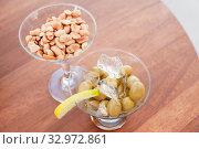 Купить «Green olives with lemon and ice and peanuts in glasses», фото № 32972861, снято 6 января 2020 г. (c) EugeneSergeev / Фотобанк Лори
