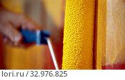 Купить «Painting a red wall with yellow paint using a roller», видеоролик № 32976825, снято 24 января 2020 г. (c) Константин Шишкин / Фотобанк Лори