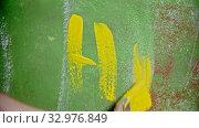 """Купить «A person writing """"HI"""" on the green wall with a yellow paint», видеоролик № 32976849, снято 24 января 2020 г. (c) Константин Шишкин / Фотобанк Лори"""