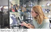 Young attractive woman choosing semiprecious stones adornments in glass showcase of jewelry store. Стоковое видео, видеограф Яков Филимонов / Фотобанк Лори