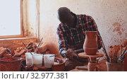 Купить «Professional African American male potter painting ceramic pot in pottery workshop», видеоролик № 32977381, снято 6 апреля 2020 г. (c) Яков Филимонов / Фотобанк Лори