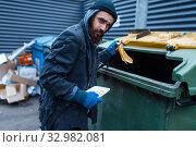 Купить «Male bearded beggar searching food in trashcan», фото № 32982081, снято 26 октября 2019 г. (c) Tryapitsyn Sergiy / Фотобанк Лори