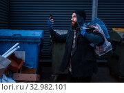 Купить «Happy beggar found mobile phone in trashcan», фото № 32982101, снято 26 октября 2019 г. (c) Tryapitsyn Sergiy / Фотобанк Лори